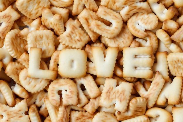 Valentinstag, liebeswort bestanden aus mit den plätzchenbuchstaben, die auf holz vereinbart wurden