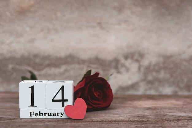 Valentinstag mit 14. februar. hölzerner weißer blockkalender, rotrose und rotes herz auf hölzernem tabellenhintergrund mit kopienraum