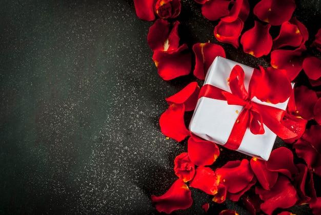 Valentinstag, mit den rosafarbenen blumenblumenblättern und weiß wickelte geschenkbox mit rotem band, auf dunklem stein, draufsicht copyspace ein
