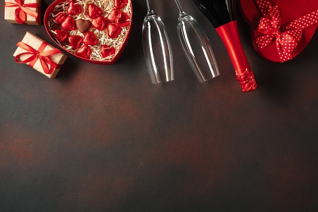 Valentinstag mit einer schachtel pralinen in form eines herzens mit einer flasche champagner mit gläsern und einer notiz.