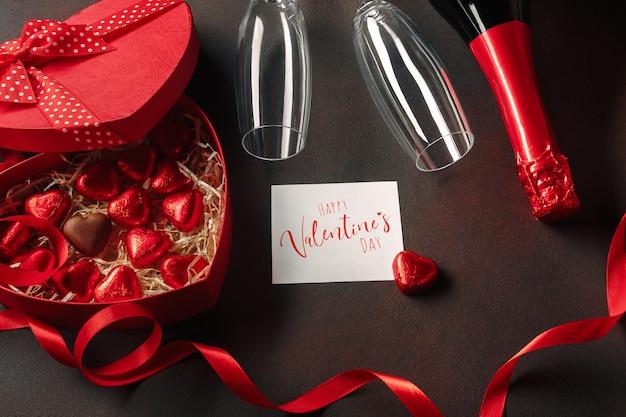Valentinstag mit einer schachtel pralinen in form eines herzens mit einer flasche champagner mit gläsern und einer notiz