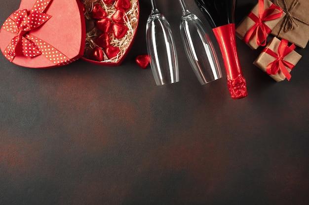 Valentinstag mit einer schachtel pralinen in form von herzgeschenken und champagner.