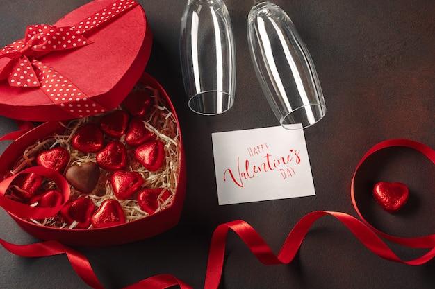 Valentinstag mit einer schachtel roten pralinen in form eines herzens mit einer flasche champagner mit gläsern und einer notiz