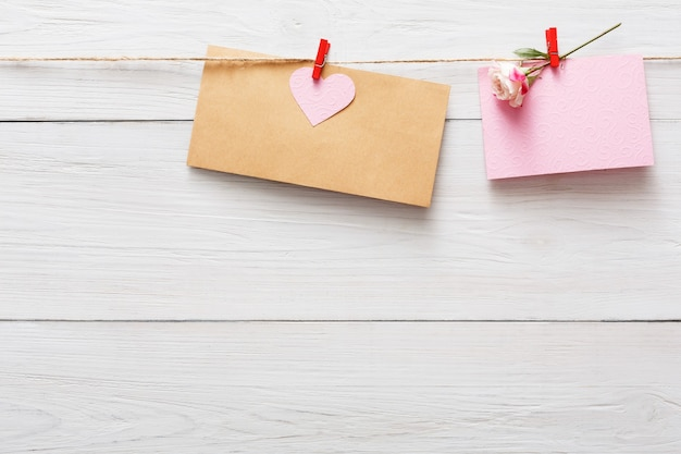 Valentinstag mit herz auf wäscheklammern und papierkarte mit rosenblüte auf rustikalen holzbrettern