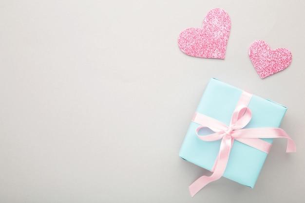 Valentinstag mit rosa herzen und geschenkbox auf grau