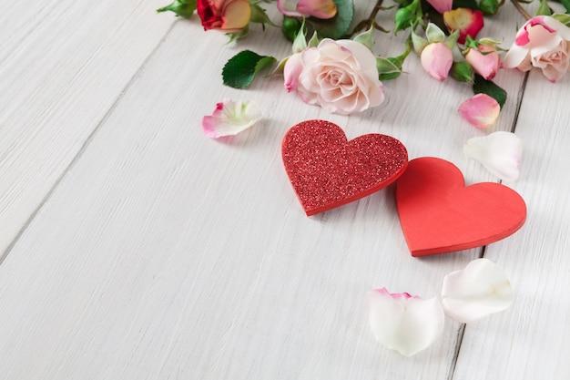 Valentinstag mit rosa rosenblütenblättern und handgefertigten holzherzen auf weißem rustikalem holz