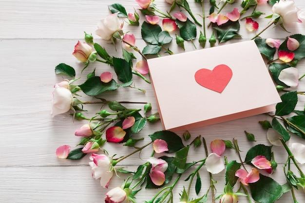Valentinstag mit rosa rosenblumen und handgemachter papierkarte mit herzen, draufsicht auf weißem rustikalem holz