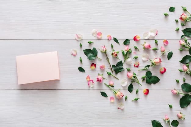 Valentinstag mit rosa rosenblumenherz und handgemachter papierkarte mit kopienraum auf weißem rustikalem holz