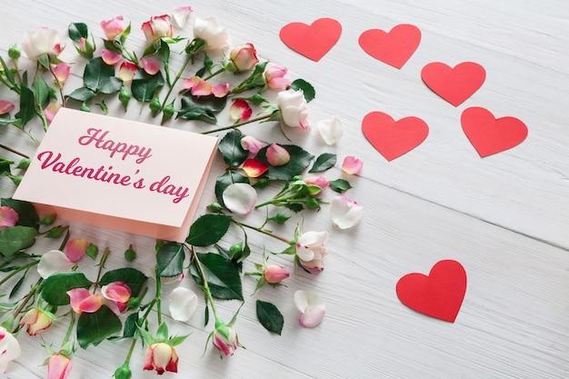 Valentinstag mit rosa rosenblumenkreis und handgemachter papierkarte mit kopienraum und herzen auf weißem rustikalem holz