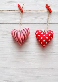 Valentinstag mit rot genähtem kissen diy handgemachte herzen paar grenze auf wäscheklammern mit rosenblüte auf rustikalen holzbrettern