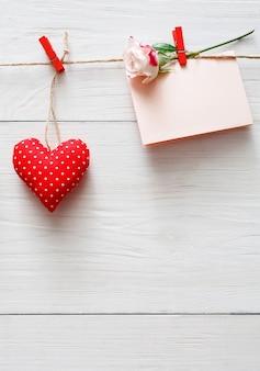 Valentinstag mit rotem kissen genähtes herz auf wäscheklammern und papierkarte mit rosenblüte auf rustikalen holzbrettern