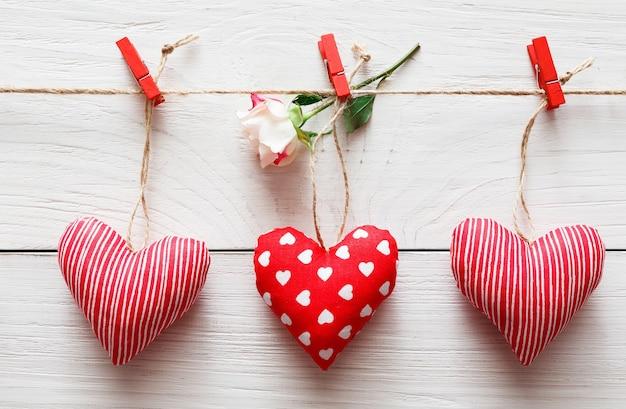 Valentinstag mit rotem papierherzenreihenrand auf wäscheklammern mit rosenblume auf rustikalen holzbrettern
