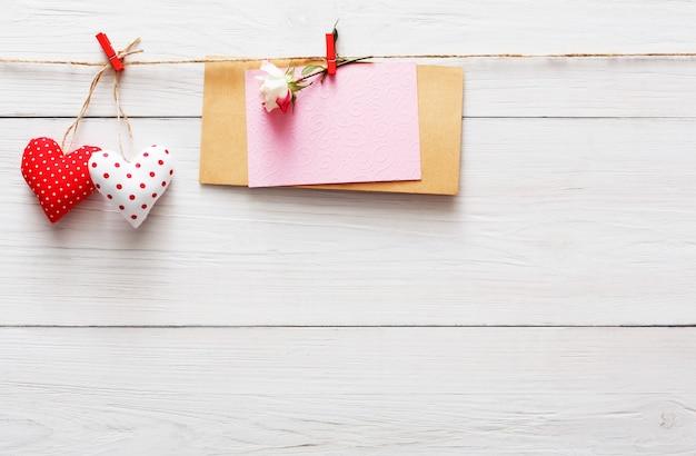 Valentinstag mit rotem papierherzenreihenrand auf wäscheklammern und papierkarte mit rosenblume auf rustikalen holzbrettern