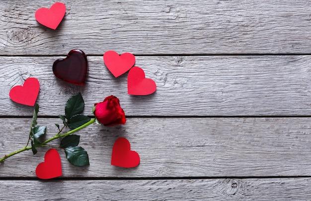Valentinstag mit roter rosenblume, glänzendem glasherz und papierkarten auf rustikalem holz