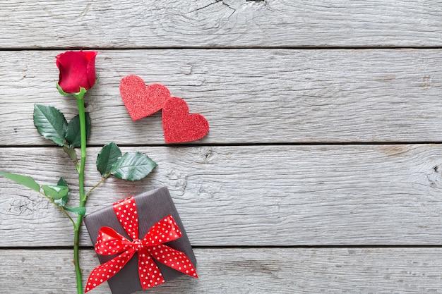 Valentinstag mit roter rosenblume, handgefertigten papierherzen und geschenkbox auf rustikalem holz