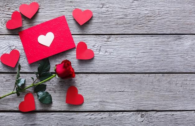 Valentinstag mit roter rosenblume, handgemachten papierherzen und karte auf rustikalem holz