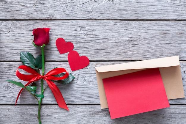 Valentinstag mit roter rosenblume und handgemachten papierherzen und grußkarte im umschlag auf rustikalem holz