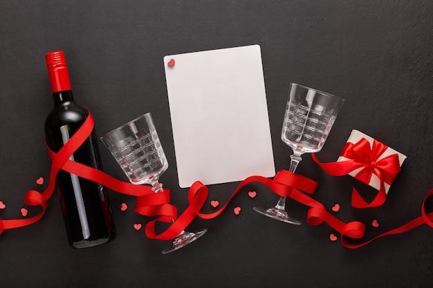 Valentinstag mit wein und geschenk, leeres blatt für text