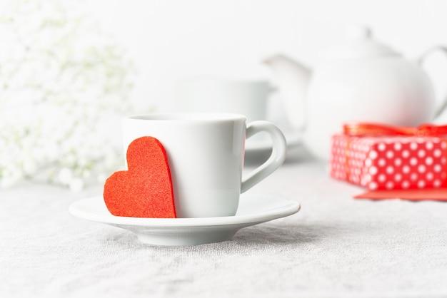 Valentinstag. morgenfrühstück für zwei mit tee, geschenk, blumen. rotes filzherz