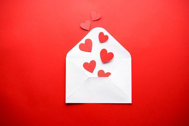 Valentinstag. muttertag hintergrund. weißer umschlag mit roten herzen auf einem roten hintergrund, flache lage.
