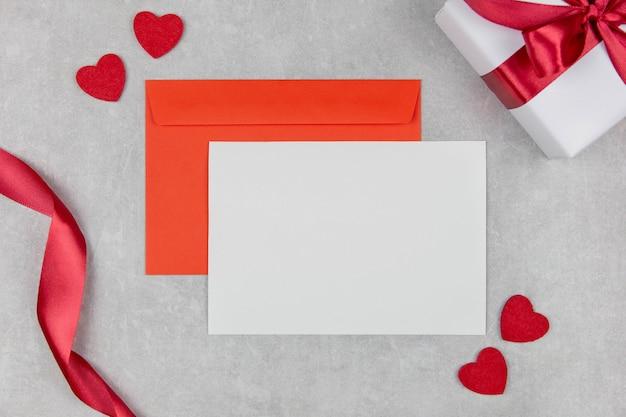 Valentinstag, muttertag oder hochzeit wohnung lag mit leeren grußkarten modell und umschlag auf hellem beton mit herzen konfetti.