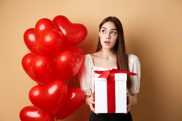 Valentinstag nachdenkliches süßes mädchen, das errät, wer ihr geschenk gemacht hat, das geschenk hält und neugierig auf dich schaut ...