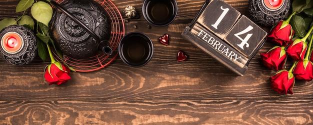Valentinstag oberfläche mit grünem tee, schwarzer teekanne, kerzen, rosen und holzkalender. valentinstag konzept. draufsicht. banner, kopierplatz