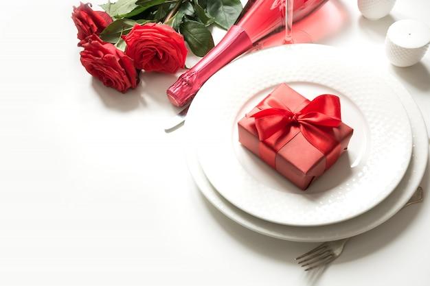 Valentinstag oder geburtstagsessen. eleganzgedeck mit champagner und rotrose.