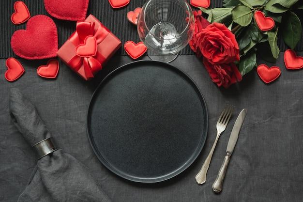 Valentinstag oder geburtstagsessen. romantische tischdekoration mit roter rose auf schwarzer leinentischdecke.