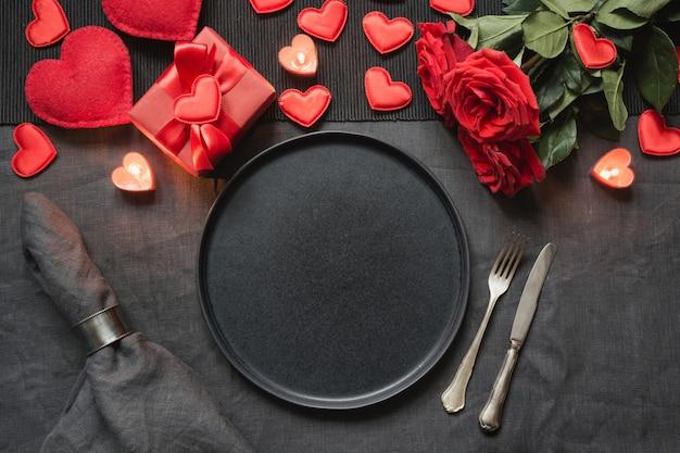 Valentinstag oder geburtstagsessen. romantisches gedeck mit rotrose auf schwarzer leinentischdecke.