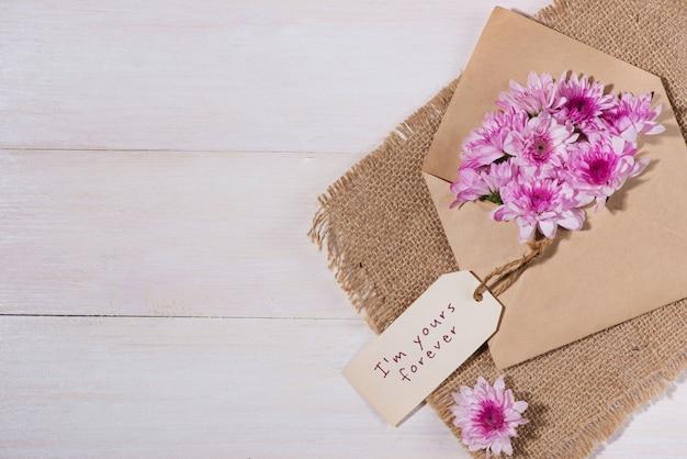 Valentinstag. papieranhänger mit braunem umschlag und rosa blumen auf holztisch.