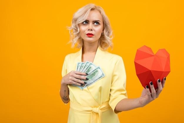 Valentinstag . porträt eines denkenden mädchens mit den roten lippen mit einem roten herzen gemacht vom papier und von den dollarscheinen in den händen auf einem gelb