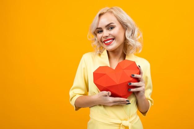 Valentinstag . porträt eines glücklichen blonden mädchens mit make-up mit dem herzen 3d gemacht vom papier auf gelb