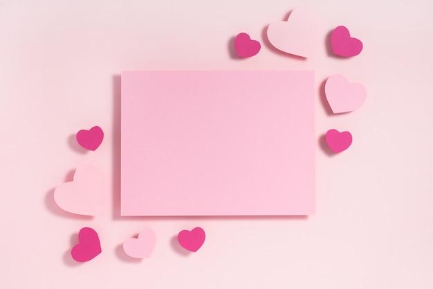 Valentinstag-rahmenzusammensetzung. lila und rosa herzen und leeres blatt papier auf pastellrosa. draufsicht, flache lage, copyspace.