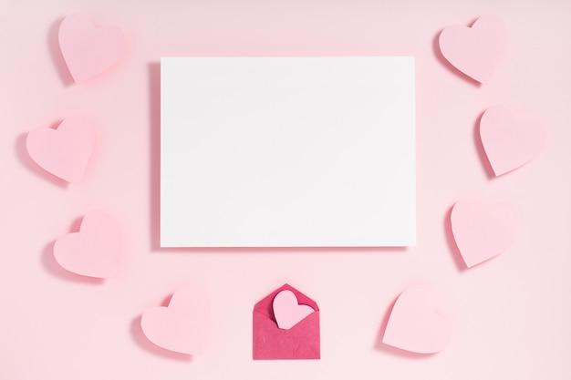 Valentinstag-rahmenzusammensetzung. rosa herzen vom umschlag und vom blatt papier auf pastellrosa. draufsicht, flache lage, copyspace.