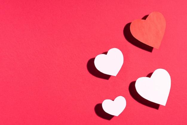Valentinstag-rahmenzusammensetzung. rote weißbuchherzen auf rot. draufsicht, flache lage, copyspace