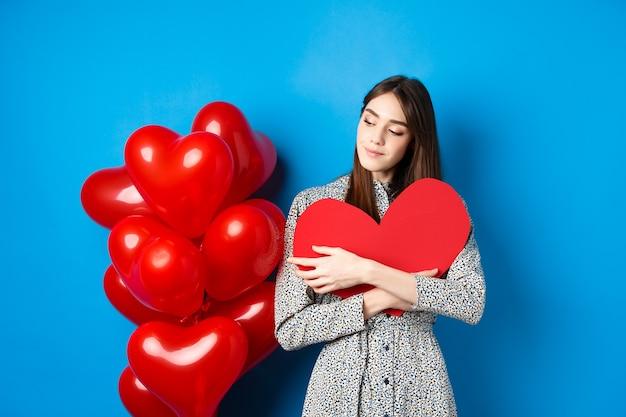 Valentinstag. romantische hübsche frau im kleid, das großen roten herzausschnitt umarmt und verträumt aussieht, an liebe denkend, auf blauem hintergrund stehend.