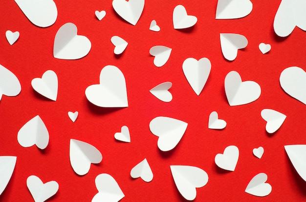 Valentinstag romantischer hintergrund. weißbuchherzen am roten hintergrund, draufsicht.