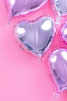 Valentinstag romantisches designkonzept - schöner echter folienballon in herzform einzeln auf hellrosa hintergrund, draufsicht, flache lage, über der fotografie.