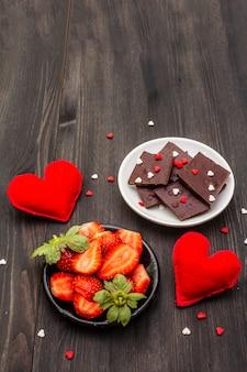 Valentinstag romantisches konzept. schokolade, frische reife erdbeere, rote filzherzen. süßspeise für verliebte.