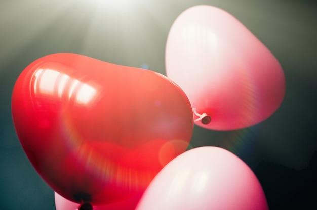 Valentinstag romantisches liebeskonzept vintage rot rosa ballons herzform fliegen durch sonnenstrahlen
