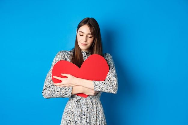 Valentinstag romantisches mädchen im kleid, das großen roten herzausschnitt umarmt, augen schließen und mit verträumtem lächeln lächeln ...
