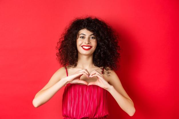Valentinstag. romantisches mädchen mit lockiger frisur im abendkleid, lächelnd und herzzeichen zeigend, sagen, ich liebe dich auf liebesfeiertag, stehend über rotem hintergrund.