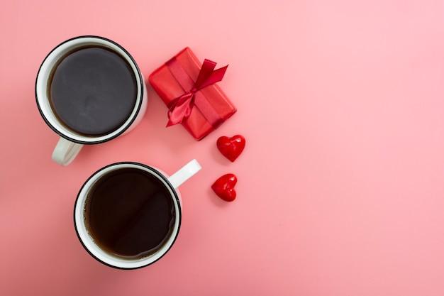 Valentinstag rosa frühstück. flache lageansicht von zwei schalen und von roten geschenkboxen.