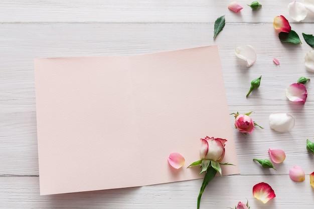 Valentinstag, rosa rosenblumen und blütenblätter verstreut auf weißem rustikalem holz und offener leerer grußkarte