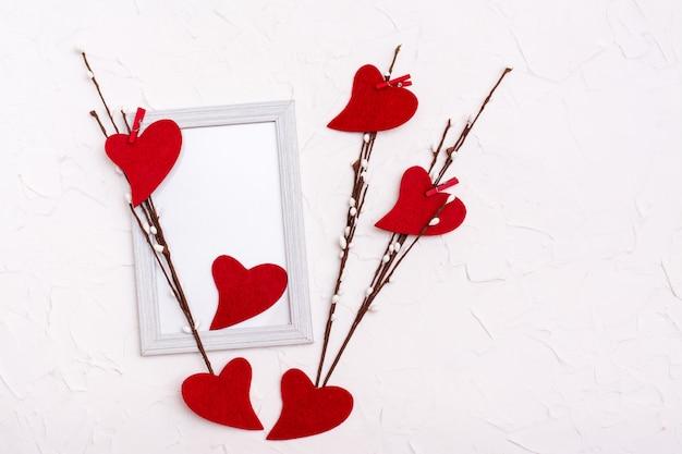 Valentinstag. rote herzen aus filz auf weidenzweigen auf einem leeren fotorahmen