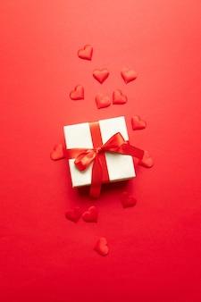 Valentinstag . rote herzen, kraftpapierüberraschungskasten mit bogen auf einem rot. flache lage, draufsicht, copyspace minimales konzept für geburtstag, muttertag oder hochzeit.