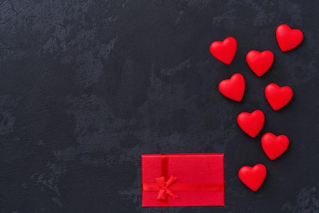 Valentinstag, rote herzen und geschenkbox auf schwarzem hintergrund