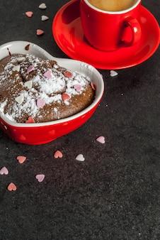 Valentinstag, rote kaffeetasse und schokoladenbecherkuchen oder schokoladenkuchen mit puderzucker und schatz formten besprüht, schwarzes, copyspace