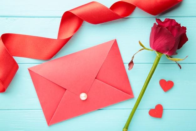 Valentinstag: roter umschlag mit einem brief und roten rosen auf blauem hintergrund. draufsicht